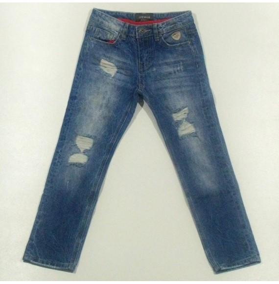 Jeans delavé con rotture